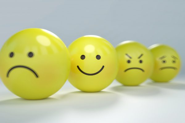 Highlighted smiley emoticon with 3 companions - unintelligent and intelligent emotions